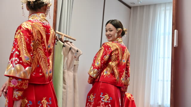 young chinese bride looking at her reflection in mirror - costume tradizionale video stock e b–roll