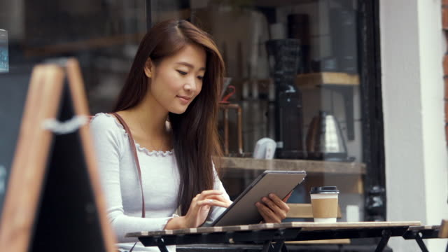 Young Chinese Student Using Tablet in Cafe (slow motion)