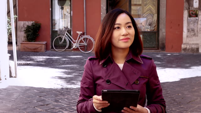 Young Chinese woman using the tablet looks around and smiles,portrait video