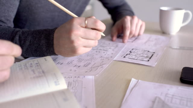 Young colleagues are analyzing blueprint at table in modern office video