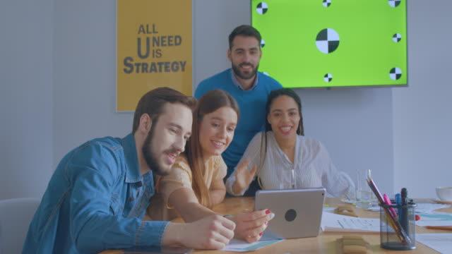 stockvideo's en b-roll-footage met de jonge collega's in zonnig bureau gebruiken tabletcomputer online vraagconferentie chromakey het glimlachen - bedrijfsstrategie