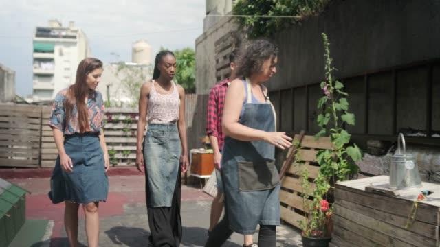 junge community-mitglieder lernen roof gardening - urban gardening stock-videos und b-roll-filmmaterial
