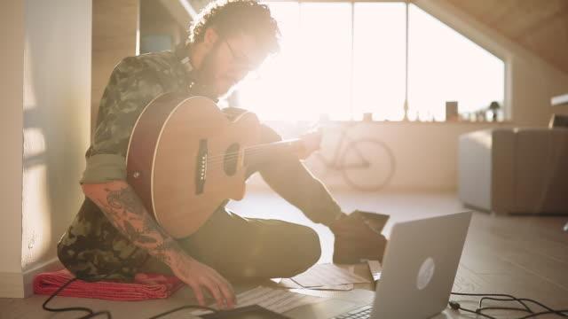 vídeos de stock e filmes b-roll de young composer recording acoustic guitar playing - compositor