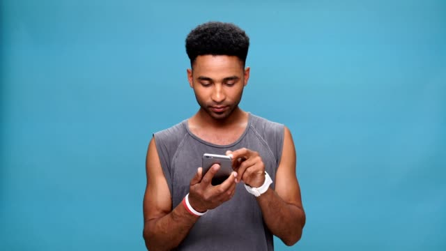 Young concentrated african man chatting by phone over blue background. video