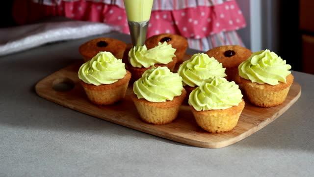 unga konditor dekorerar cupcakes med citron grädde och druva närbild - cupcake bildbanksvideor och videomaterial från bakom kulisserna