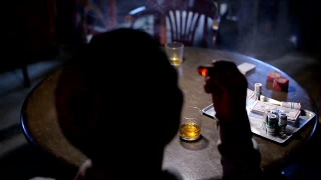 ung självsäker gangster visar upp vid bordet gaming - kriminell bildbanksvideor och videomaterial från bakom kulisserna