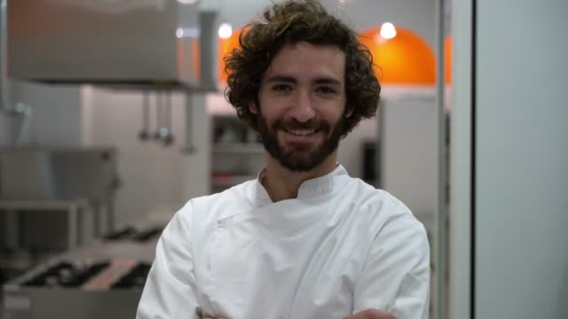 young confident male chef standing looking at the camera with arms crossed smiling - chef stock videos and b-roll footage
