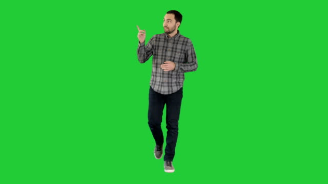 stockvideo's en b-roll-footage met jonge zelfverzekerde man in het shirt en spijkerbroek lopen naar de camera en wordt gewezen op de zijkanten op een groen scherm, chromakey - street style