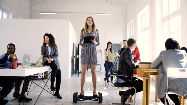 Young confident serious blonde business woman in dress riding electric gyroscooter in modern loft multiethnic office. Young confident serious blonde business woman in dress riding electric gyroscooter in modern loft multiethnic office. Successful female leader controlling working process moving around on scooter. coworking stock videos & royalty-free footage