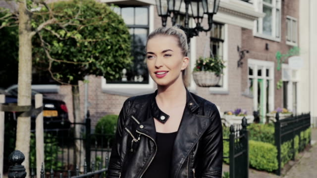 Young confident woman walking in the city streets during sunny day. video