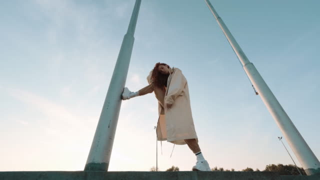 Young Contented Girl. Urban Fashion Concept. Young Contented Girl. Urban Fashion Concept. Pretty Girl With Long Hair. She Holds One Foot On Vertical Electric Pole. urban fashion stock videos & royalty-free footage