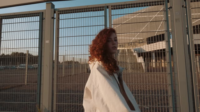 Young Contented Girl Walking Down The Street. Young Redheaded Girl Walking Down The Street. Girl Has Long Curly Hair. Urban Fashion Concept. urban fashion stock videos & royalty-free footage