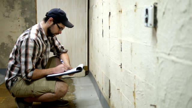 young contractor examines interior french drain in unfinished basement - basement stock videos & royalty-free footage