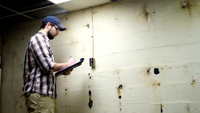vidéos et rushes de jeune entrepreneur ressemble et porte sur le mur du sous-sol et interrupteur électrique - inspecteur