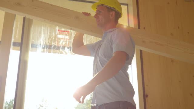 närbild: ung entreprenör bär en hård hatt bär en stor planka över huset - solar panel bildbanksvideor och videomaterial från bakom kulisserna