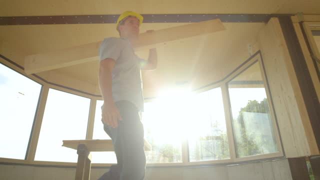 lågvinkel ung entreprenör bär en hård hatt bär en stor planka över huset - solar panel bildbanksvideor och videomaterial från bakom kulisserna