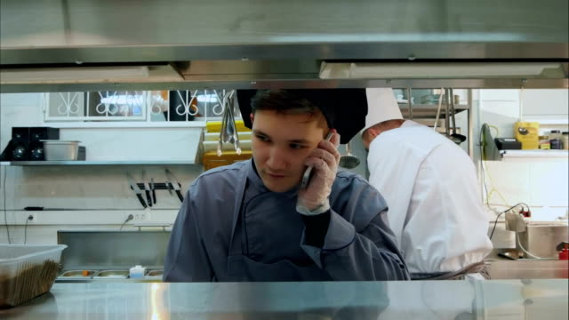 Young cook trainee talking on the phone in the professional kitchen video