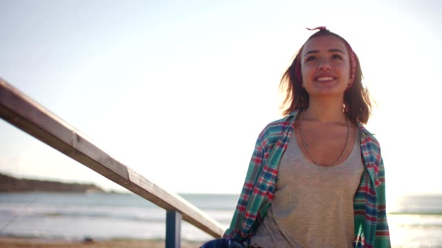 Young cool girl walking with skateboard at the beach video