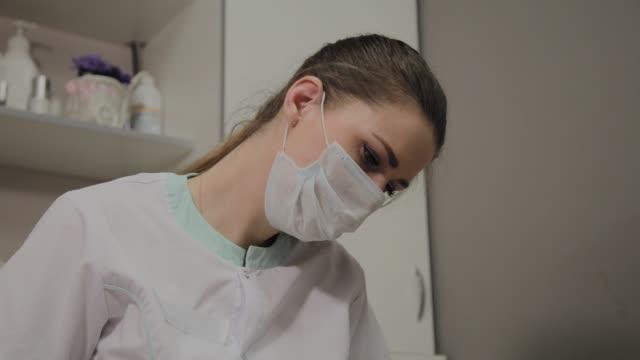 young cosmetologist at work, portrait of a beautiful cosmetologist in mask - kosmetyczka praca w salonie piękności filmów i materiałów b-roll