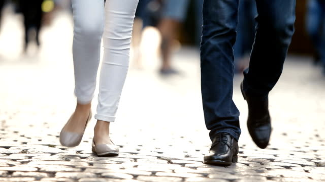 Young couple, a man and a woman, walk around the city, along the pavement. Legs close-up. video