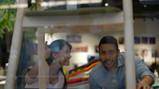 vídeos de stock, filmes e b-roll de jovem casal admirando o design de uma cadeira em uma loja de móveis - mobília