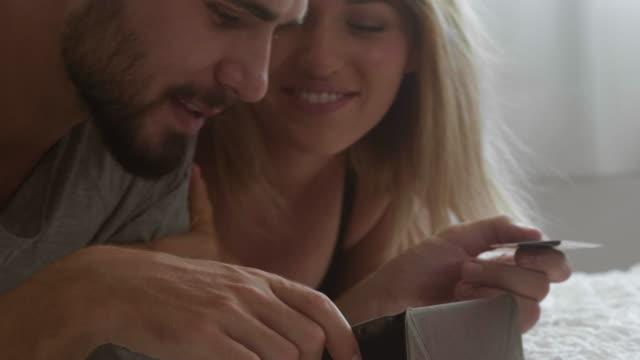 young couple and cradit card - fare una prenotazione video stock e b–roll
