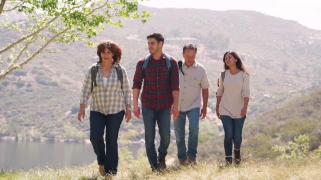 若いカップルや山・湖を歩くシニアの親 - 対面点の映像素材/bロール