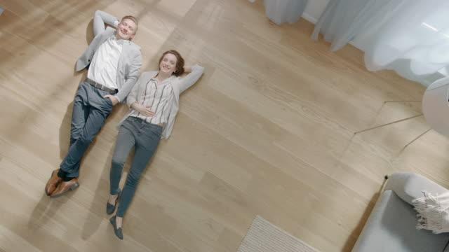 ungt par ligger på en trä golv i en lägenhet. de är lyckliga, leende och skratta. mysigt vardags rum med modern interiör, grå soffa och parkett golv i trä. kamera bilder i topp läge. - golv bildbanksvideor och videomaterial från bakom kulisserna