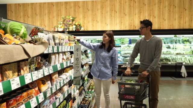若いカップルがショッピング カートでショッピングします。 ビデオ