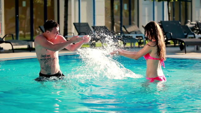 Young couple are splashing the water in the swimming pool