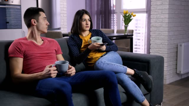 Young couple arguing about TV channels on sofa video