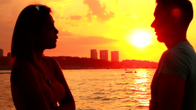 young couple at beach talk and kiss at sunset video