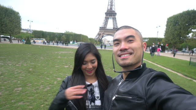 CNEUTRV1093 Young couple at Eiffel tower taking a selfie photo video