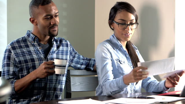 Young couple at home paying bills, smiling video