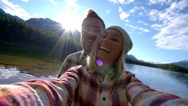 Young couple by the mountain lake taking a selfie portrait at sunrise, Canada video