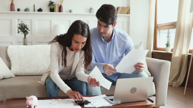 Young couple calculating bills or taxes making savings concept