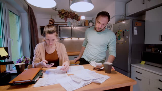 Young couple calculating their domestic budget together in the kitchen, try to safe money, having stresses video