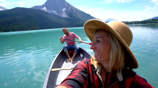 Young couple canoeing on a beautiful lake in Canada, taking selfies video