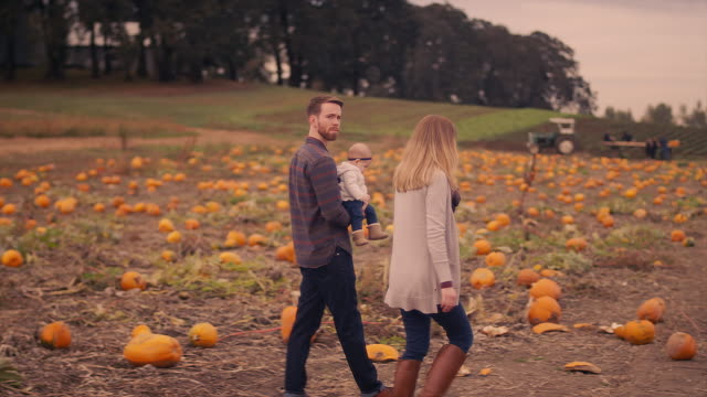 A young couple carrying their baby around at a pumpkin patch