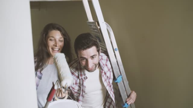 Young couple carrying wall painting tools in their new house Young couple renovating their new house, they are carrying wall painting tools and going upstairs to their apartment: lifestyle and home renovation concept renovation stock videos & royalty-free footage