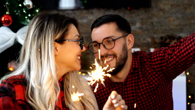 Young couple celebrate Christmas at home near Christmas tree
