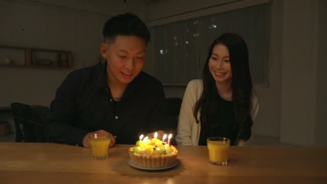 Young couple celebrating birthday with fruit cake