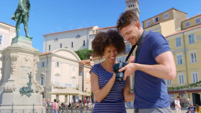 Young couple checking the photos they just took with the camera as they stand in the town square