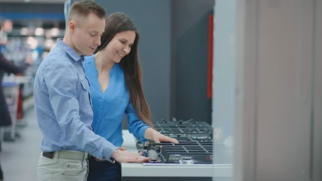 vídeos de stock e filmes b-roll de young couple chooses cooktop in store of household appliances - cooker happy