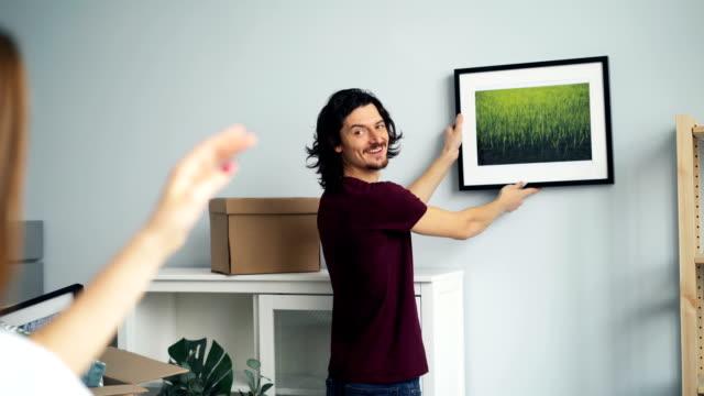 ungt par väljer plats för bild på väggen i nytt hus efter flytten - fotoram bildbanksvideor och videomaterial från bakom kulisserna