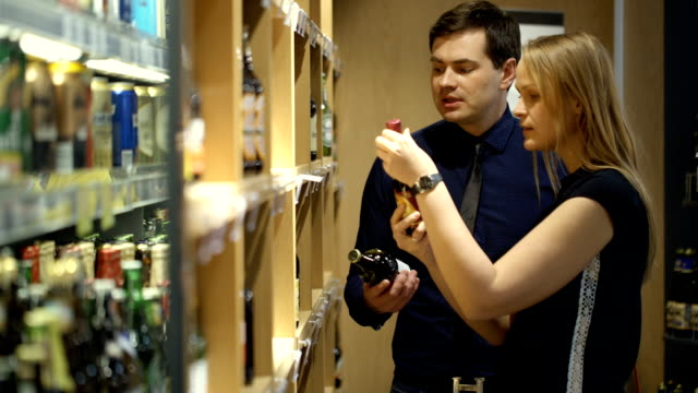 Young couple choosing wine in the shop video