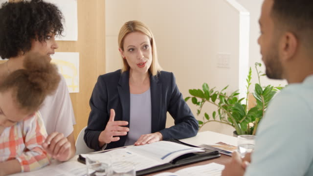 Young couple consulting with female insurance agent at their home video
