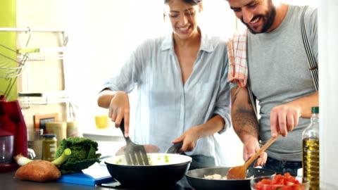 vidéos et rushes de jeune couple de cuisiner à la maison. 4k - jeune couple