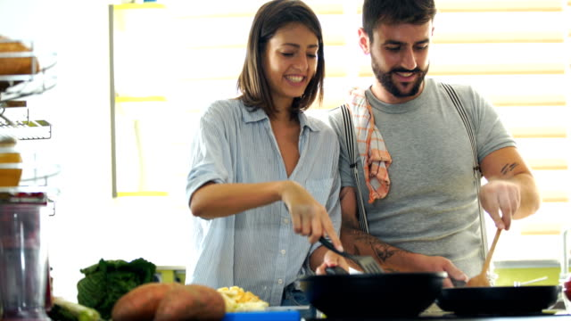 Young couple cooking at home. 4k Closeup front view of attractive mid 20's couple preparing lunch together and having fun. This is the part of their Sunday routine. frying pan stock videos & royalty-free footage
