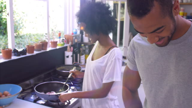 Young Couple Cooking Breakfast In Kitchen Together